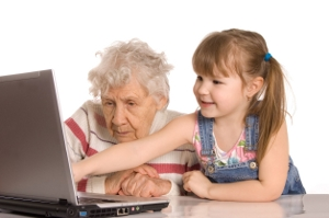 child leading grandparent at computer